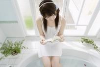 坐在浴缸上听歌看书的美女图片素材