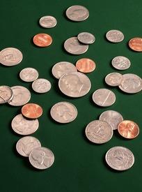 绿色背景上散乱的各国硬币