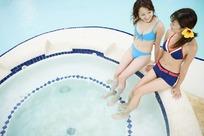 游泳池边泡脚的性感美女摄影图片