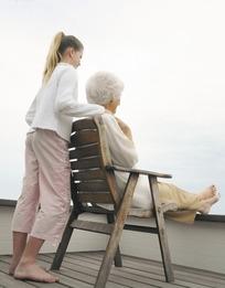 背对着女孩手搭在座椅上老人肩膀的外国人