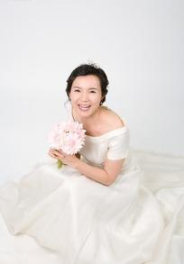 穿着白色礼服手拿捧花的中年女人