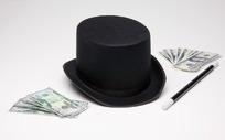黑色魔术帽与魔术棒旁边的外币