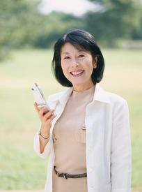 草地上拿着电话的中年女人