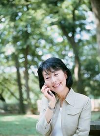 树荫下打电话的中年女人