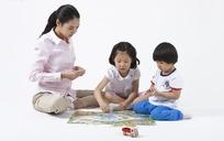 坐在地上和妈妈玩拼图的两个小孩