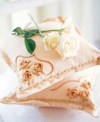 上面放着白色玫瑰花裸色的精美抱枕