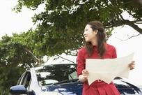 坐在车头手拿地图的红衣女子