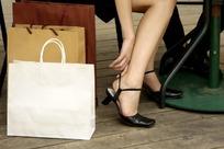 购物袋和坐着提鞋的女人脚部特写