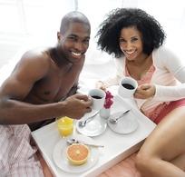 躺在床上微笑用餐的外国情侣