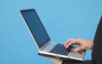 左手托着笔记本电脑右手按键盘的男子的手