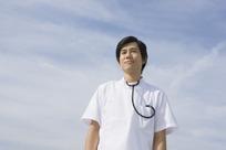 蓝天下穿着白色工作服带着听诊器的男护士