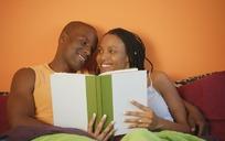 躺在床上看书的一对外国情侣