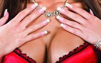 手放在带红色胸罩的胸部上的特写