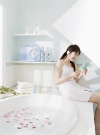 坐在浴缸旁微笑着听歌看纸片的美女