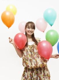 手上拿着气球微笑的长发美女