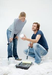 拿着一盒墙面漆的外国男人和站在旁边的女人