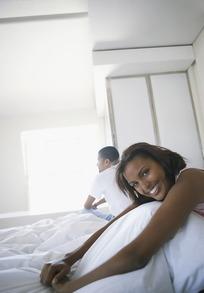 曲坐在床上的美女