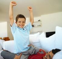 骑在爸爸肚子上举起双手微笑的小男孩