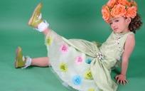 戴着花朵坐在地上单腿翘起的小女孩