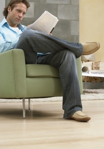 坐在沙发上翘腿看文件思考问题的外国男人