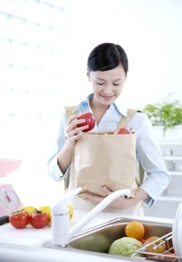 手捧装有水果蔬菜的包装袋女士特写照片
