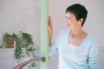 扶着门柱侧头微笑的中年女人