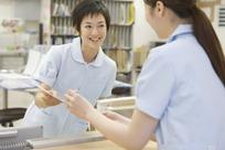 护士微笑拿着病历给医生签字