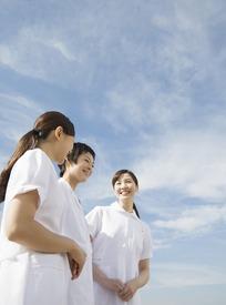 蓝天白云下三个微笑的美女护士