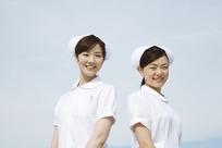 蓝天下戴护士帽微笑的两个女护士