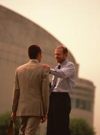 手搭在伙伴肩上微笑的外国职业男士