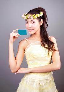 手拿空白绿色卡片头戴花环的美女