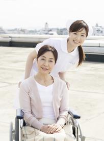 坐在轮椅上的老太太和女护士微笑合影