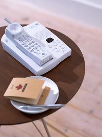 茶色桌子上的白色电话机