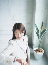 美女 职业装-看手表的职业装美女和一旁的花盆