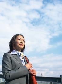 美女 湖南-蓝天白云下握皮包微笑的职业装美女