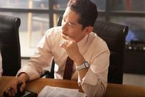办公桌前拿着笔思考问题的男人