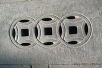 石头雕刻的三枚圆形方孔铜钱图案