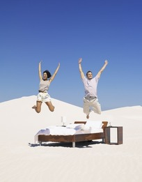 沙漠中床上跳跃的情侣