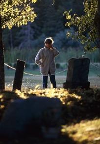墓碑前站立着的老妇人