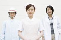 微笑的手放身前的护士和其它两个人