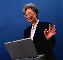 站在电脑前演讲的老妇人