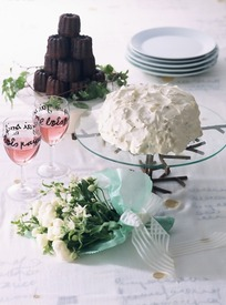 桌子上的白色花朵盛着红酒的高脚杯和盘子里的奶油