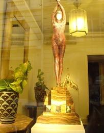 黄色室内光亮吊灯和灯下伸着双手的站立裸体女人雕塑
