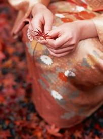 蹲着拿着一片枫叶的日本女人