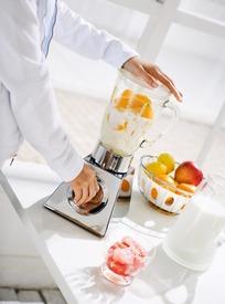 正在用榨汁机榨橙汁的双手图片_酒水饮料图片