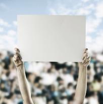 模糊人群中双手举着空白牌子