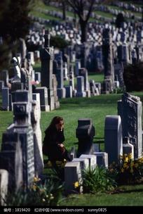 墓地里蹲着的女孩和墓碑