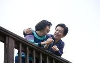 微笑靠在栏杆上聊天的中年夫妻