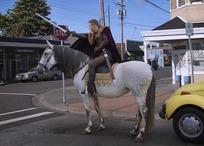 骑马走在小镇道路上的外国男人