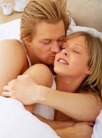 依偎在床上的一对幸福情侣